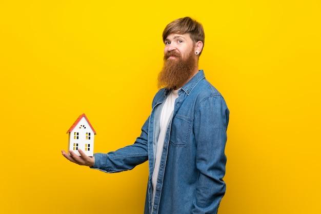 Roodharigemens met lange baard over geïsoleerde gele muur die een klein huis houden