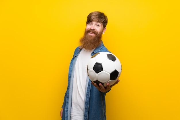 Roodharigemens met lange baard over geïsoleerde gele muur die een voetbalbal houden