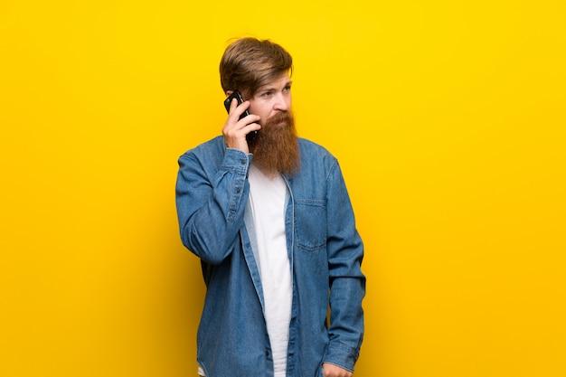 Roodharigemens met lange baard over geïsoleerde gele muur die mobiele telefoon met behulp van