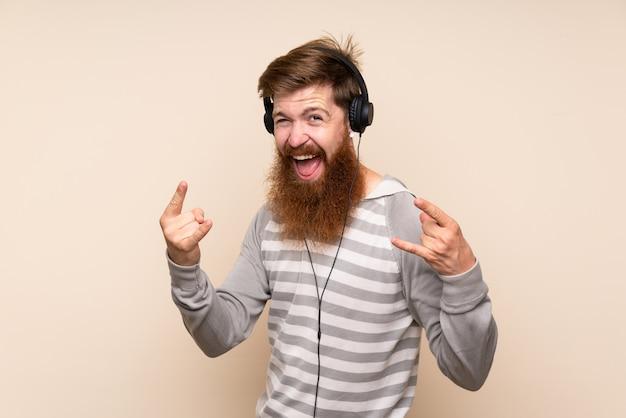 Roodharigemens met lange baard over geïsoleerde muur gebruikend mobiel met hoofdtelefoons en het dansen