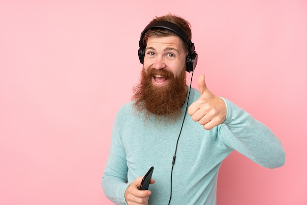 Roodharigemens met lange baard over geïsoleerde roze het luisteren muziek en met omhoog duim