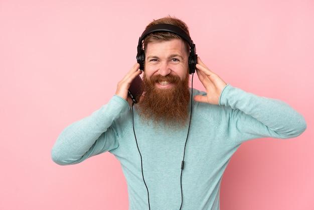 Roodharigemens met lange baard over geïsoleerde roze muur het luisteren muziek