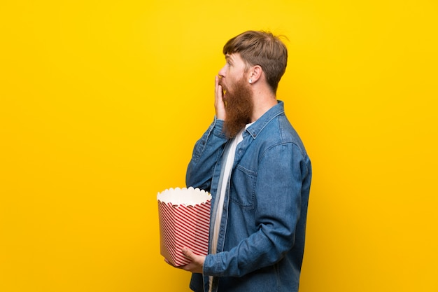 Roodharigemens met lange baard over gele muur die een kom popcorns houden