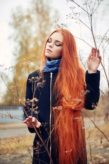 Roodharigevrouw die in de herfst de stad lopen. koude
