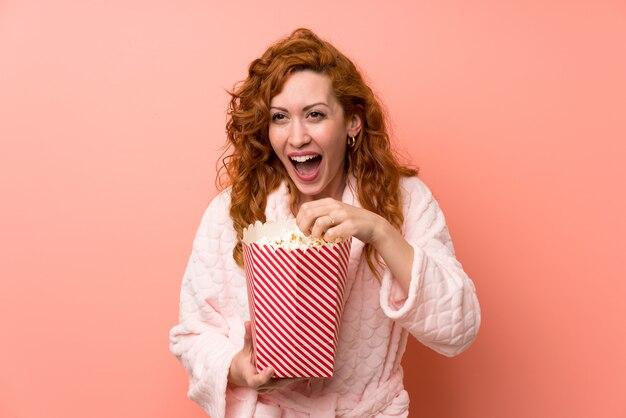 Roodharigevrouw die in peignoir popcorns eten