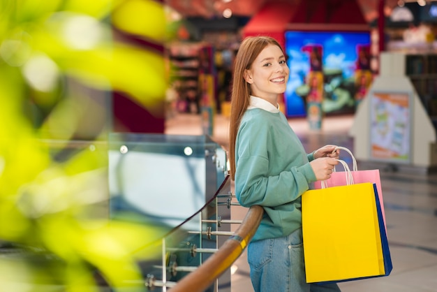 Roodharigevrouw die kleurrijke het winkelen zakken houden