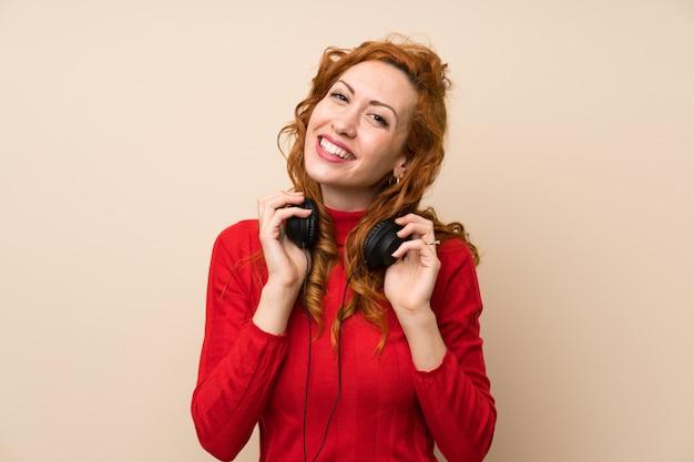 Roodharigevrouw die met coltrui aan muziek met hoofdtelefoons luisteren