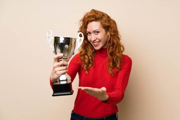 Roodharigevrouw die met coltrui een trofee houden