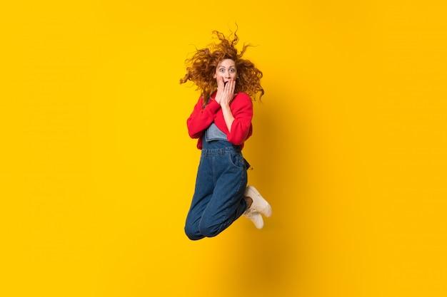 Roodharigevrouw die met overall over geïsoleerde gele muur springen