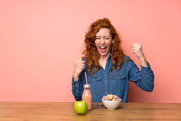 Roodharigevrouw die ontbijtgraangewassen en fruit hebben die een overwinning vieren