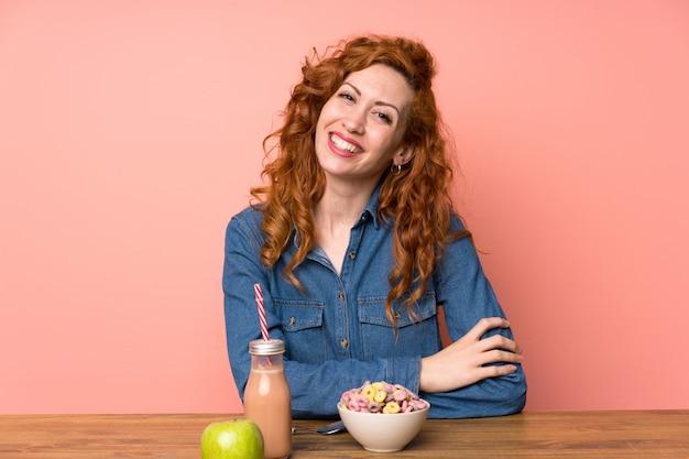 Roodharigevrouw die ontbijtgraangewassen en fruit het lachen hebben