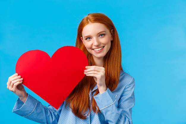 Roodharigevrouw die rood hart en het glimlachen houden