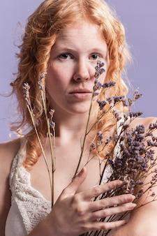 Roodharigevrouw die terwijl het houden van een boeket van lavendel stellen
