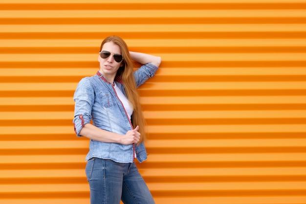 Roodharigevrouw in jeansoverhemd met zonnebril dichtbij oranje muur