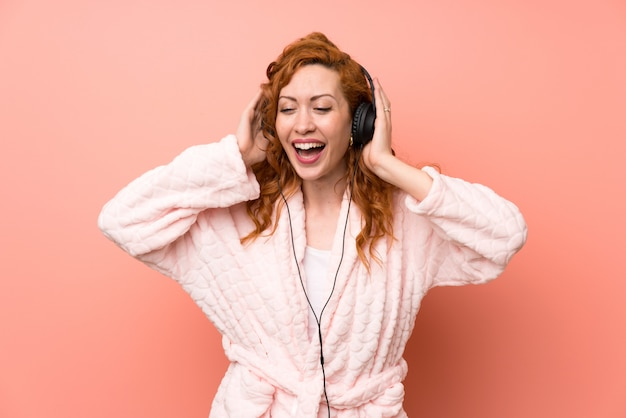 Roodharigevrouw in peignoir het luisteren muziek