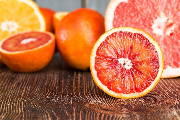 Roodoranje heerlijk oranje fruit van verschillende soorten, in tweeën gesneden tijdens de bereiding van desserts