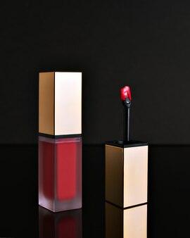 Roodroze lipgloss met zwarte achtergrond en een kwastje voor het aanbrengen van make-up