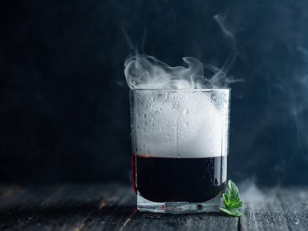 Rook in een glas met rode alcohol