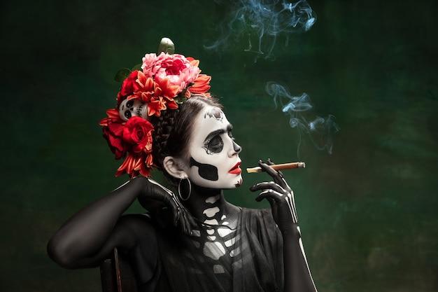 Rook. jong meisje zoals santa muerte saint dood of suikerschedel met lichte make-up. portret geïsoleerd op donkere groene studio achtergrond met copyspace. het vieren van halloween of dag van de doden.
