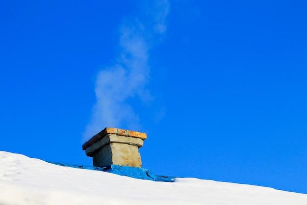 Rook uit de schoorsteen in de winter
