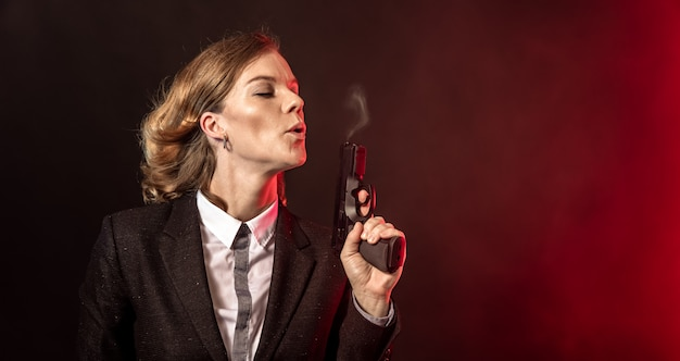 Rook uit een pistool blazen na een schot. portret van een zakenvrouw op een donkere achtergrond. banner met kopie ruimte