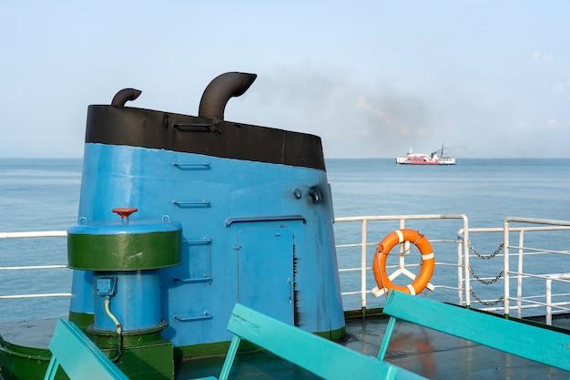 Rook uit het rookkanaal van de veerboot tijdens zee met zonlicht, zeewater en blauwe lucht op de achtergrond, thailand. aan boord, schoorsteen van een veerboot of cruiseschip, schoorsteen vervuilt de atmosfeer