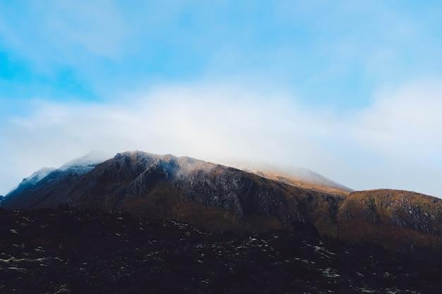 Rookwolk die uit een bergachtig landschap komt dat de hemel raakt