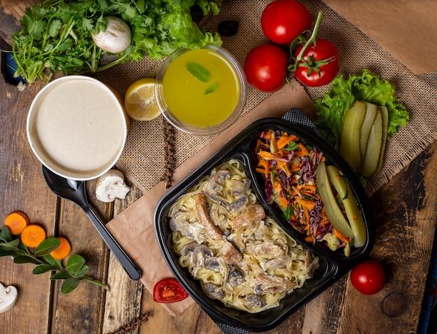 Room champignonsoep in wegwerpbeker kom geserveerd met groene groenten, champignonroom stoofpot en groentesalade