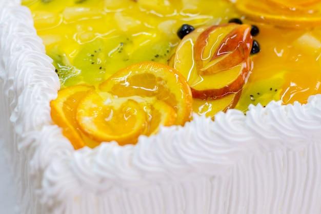 Room en plakjes fruit. appel en kiwi in gelei. vers gebakken taart. hoog gehalte aan calorieën.