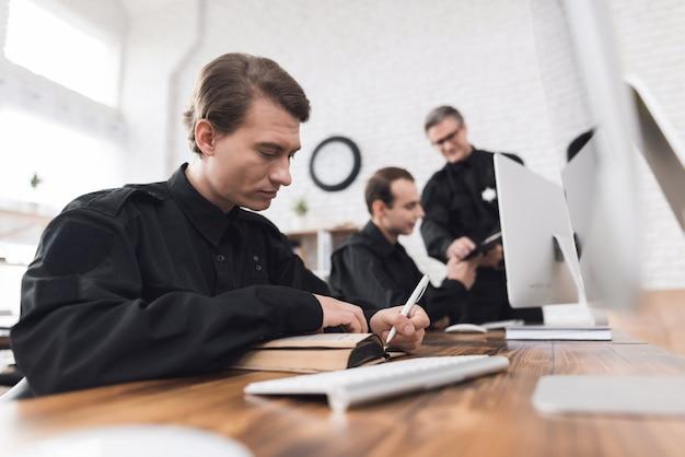 Room instrueert ondergeschikten in politiebureau.