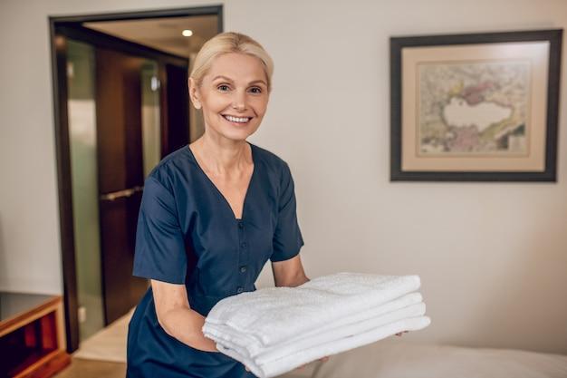 Room service. glimlachende blonde vrouw in uniform met schone handdoeken