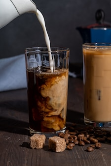 Room wordt gegoten in een glas met ijskoffie, op een houten tafel met koffiebonen en suiker.