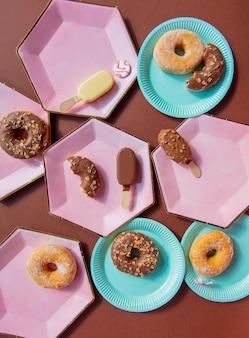 Roomijs en donuts op gekleurde platen op bruine achtergrond