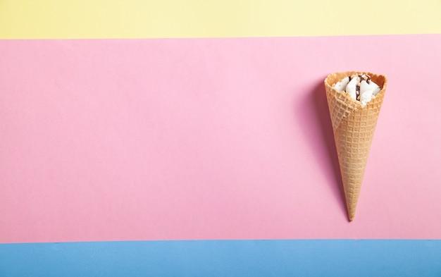 Roomijs in wafelkegel op gele, blauwe, roze achtergrond.