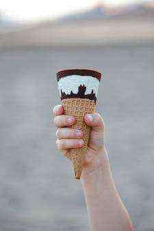 Roomijs met chocolade in een wafelkegelclose-up in de hand van een kind