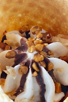 Roomijs met noten in een kegel die op witte achtergrond wordt geïsoleerd