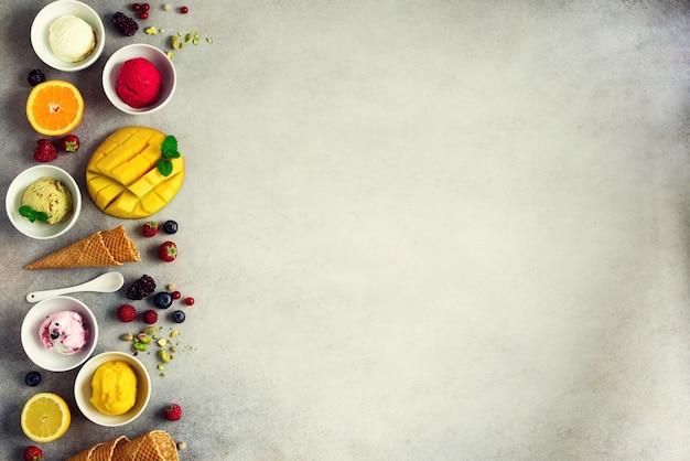 Roomijsballen in kommen, wafelkegels, bessen, sinaasappel, mango, pistache op grijs beton. de kleurrijke vlakke inzameling, legt, de zomerconcept, hoogste mening