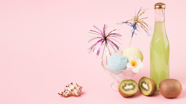 Roomijsballen met sierwandelstok op glaskom dichtbij vruchten en fles