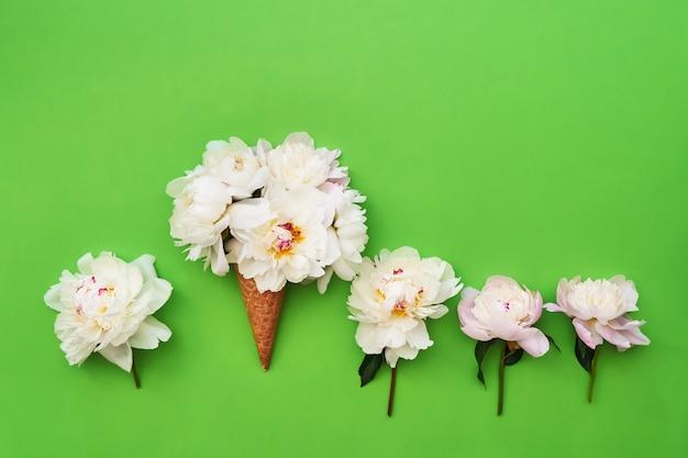 Roomijskegel met witte pioenbloemen rond op groene achtergrond.