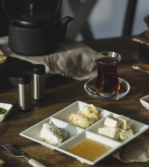 Roomkaas, honing en boter met een glas thee