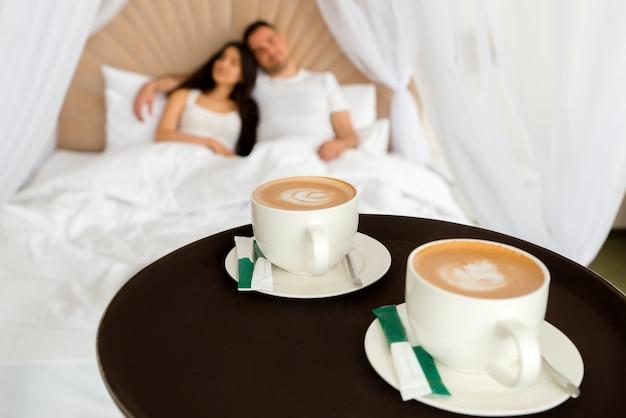 Roomservice bezorgt 2 kopjes koffie aan een hotelkamer voor een getrouwd stel dat 's ochtends in een bed ligt