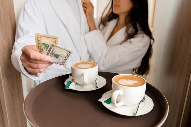 Roomservice bezorgt koffie aan een hotelkamer voor een echtpaar in badjas dat dollartips geeft