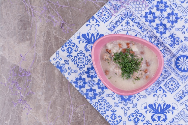 Roomsoep met bonen in bouillon geserveerd met gehakte kruiden