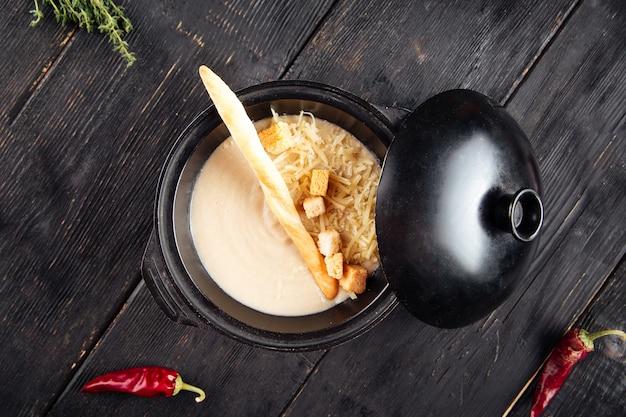 Roomsoep met crackers en geraspte kaas in gietijzeren kom op de zwarte houten