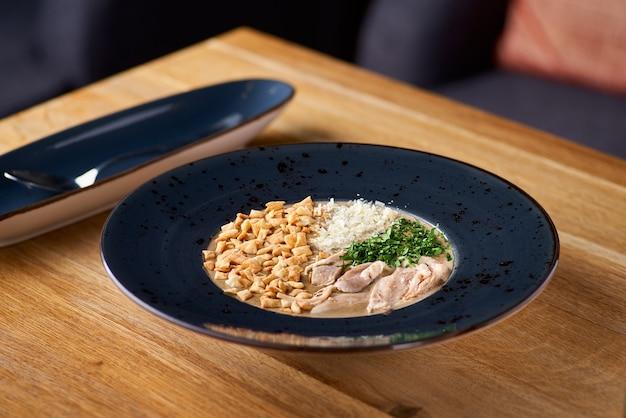 Roomsoep met vlees, noten en groenten. heerlijk diner in een close-up van de plaat op een houten tafel