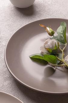 Roos in een bord op tafel, grijze pastelkleuren. romantisch minimalistisch levensstijlstilleven. verticale foto voor een liefdesverhaal.