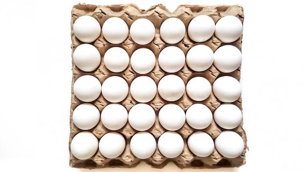 Rooster van witte eieren van dertig stukken op een wit. bovenaanzicht. paasvakantie