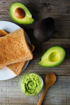 Roosteren met guacamole, avocado-plakjes. gezond eten, snack. ontbijt. houten rustieke tafel.