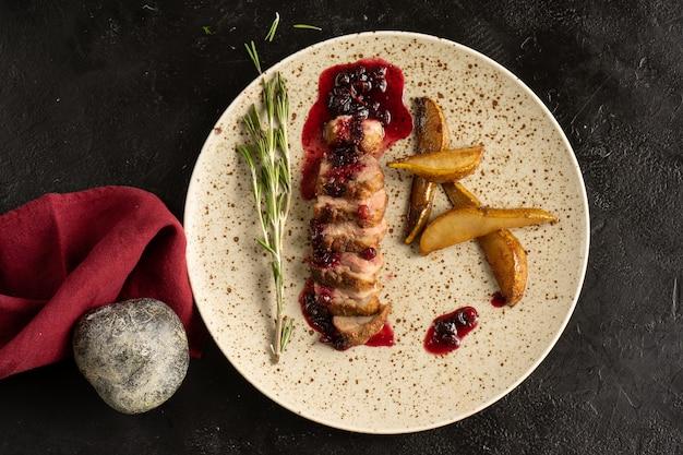 Rosbief met cranberrysaus, rozemarijn en gebakken peer. plaat met vleesschotel op een zwarte lijst. bovenaanzicht.