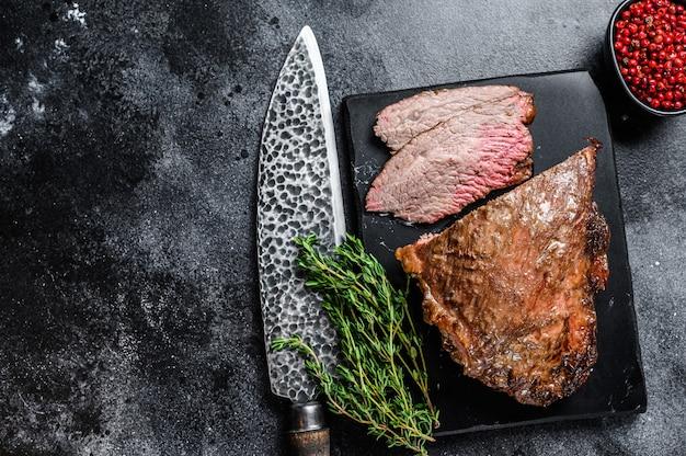 Rosbief tri tip steak bbq. zwarte achtergrond. bovenaanzicht. kopieer ruimte.